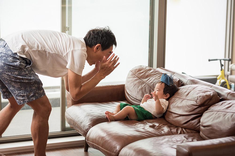 赤ちゃんをあやすパパの写真