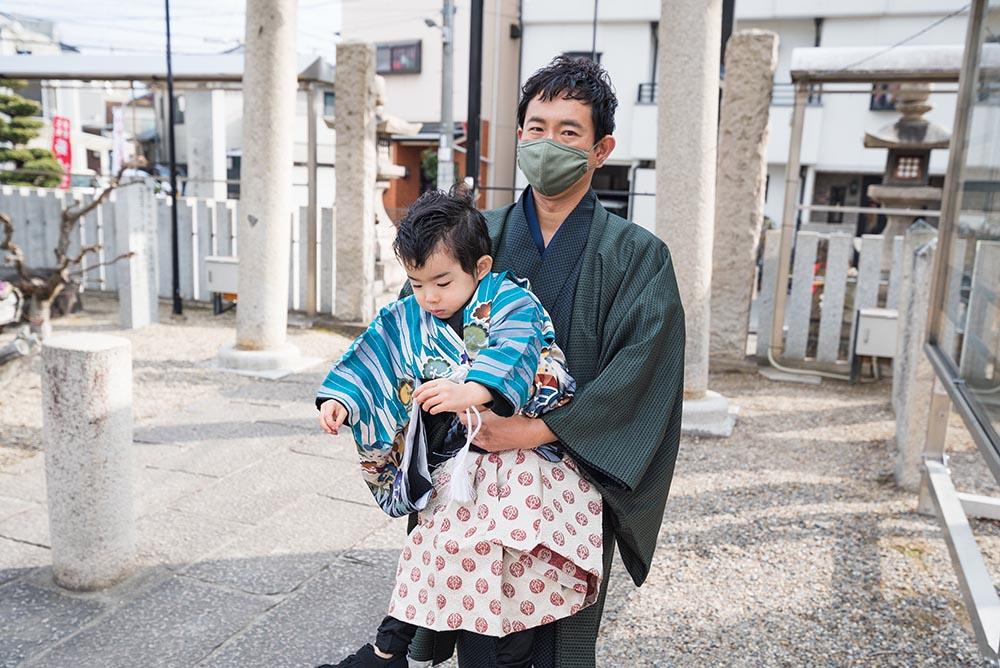 神社で遊ぶ父子の写真
